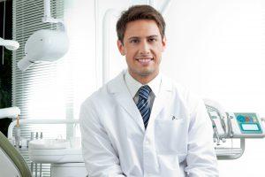 happy male dentist in dental clinic